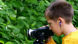 Young boy with video camera shoots film about nature of green park background Footage