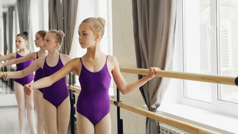 Young ballerinas in trendy ballet suits are practising arm movements and plie in Footage
