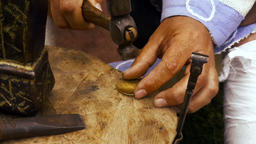 Man works with hammer and anvil coppersmith bracelet historical reconstruction Footage