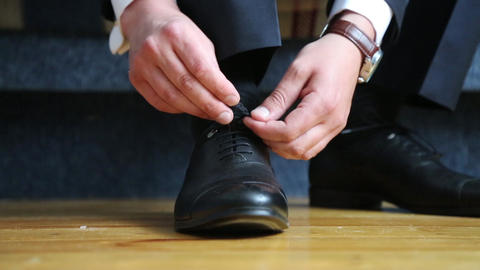 Man ties the laces on black shoes. Close-up of hands and shoes Live Action