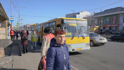 Passengers go out and get on the yellow city public bus at bus stop on city road GIF