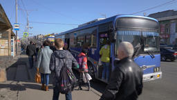 Passengers go out and get on the blue city public bus at bus stop on city road Footage