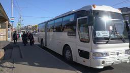Passengers enter the white intercity bus Hyundai Aero Hi Space at bus stop Footage