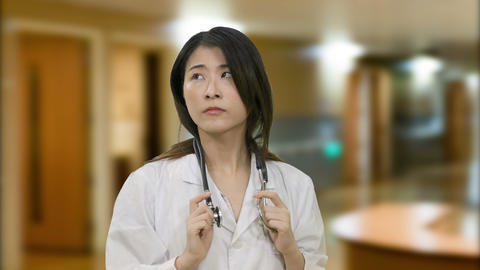 Asian female doctor in hospital thinking and has breakthrough looks at camera Footage