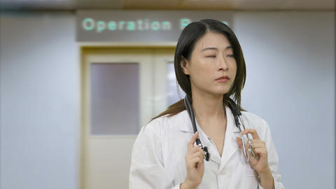 Asian female doctor in hospital looking worried outside operation room Live影片