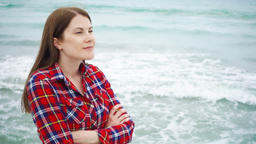 Woman look at sea waves on beach. Female traveler is cold during vacation on Footage