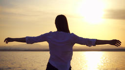 Silhouette of young woman spin at sunset on lake. Female figure dance at golden Footage