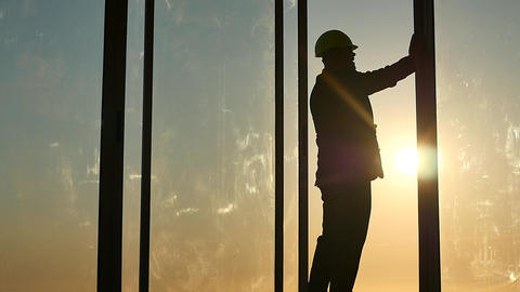 builders chief in helmet check quality of work silhouette in window frame Footage