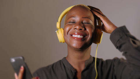happy bautiful black afro American woman with yellow headphones and mobile phone 영상물