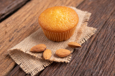 Close up a cup of almond cake against sack fabric on wooden tabl Photo