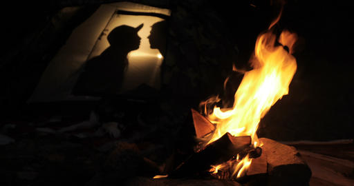 Silhouette of a kissing couple in tent near fire Footage