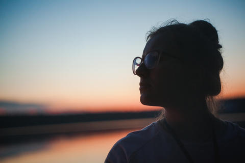 Silhouette girl in glasses sunset Photo