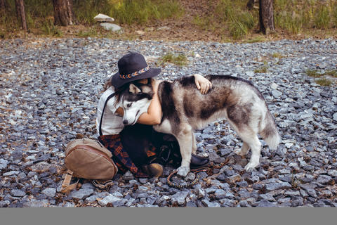 Woman embracing with dog on rocks Photo