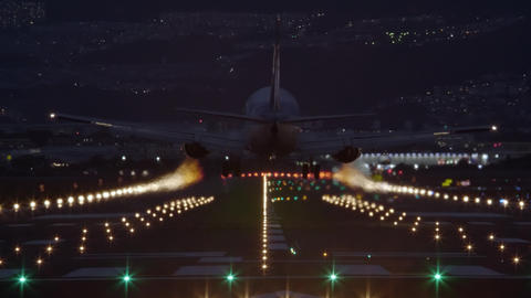 Airliner landing on the runway at night - back view GIF