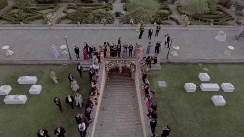 Aerial of a newlywed couple walking up the stairs of a beautiful villa Footage