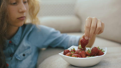 Beautiful teen girl with strawberry. Beautiful teen girl is eating a strawberry Footage