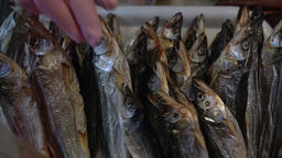 Close-up hand shows dried salted smelt fish on counter at fish market Footage
