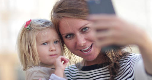 Millennial Mother taking selfie with daughter Live Action