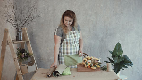 Woman choosing kraft paper for edible arrangement Live Action