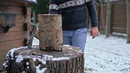 Slow Motion of a Handsome Young Man Chopping Wood with Axe near House in Winter Footage