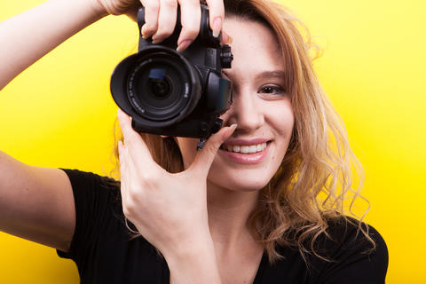 Beautiful woman holds a camera at her eye taking a picture Photo