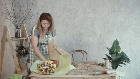 Lovely woman packing edible bouquet in kraft paper Live Action