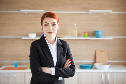 Woman in business suit posing in her kitchen フォト