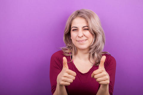 Blonde woman showing thumbs up to the camera Fotografía