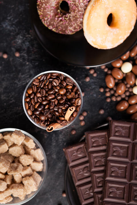 Coffee beans in a glass with cinnamon sticks next to different types of candies フォト