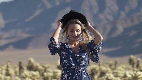 girl dresses a hat in the desert GIF