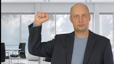 Serious businessman cheering with fist up in modern office Footage