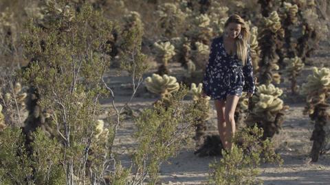 woman walks between cacti in the desert Live Action