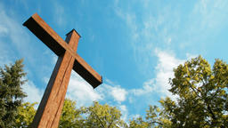 Panorama of Wooden Cross among Trees on the background of Sky and Moving Clouds Footage