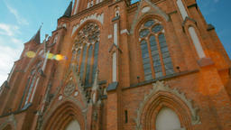 Vertical Panorama of the Church of Red Brick with Clock on Blue Sky background ビデオ