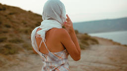 Slender Young woman in a Headscarf and Dress Goes in the Mountains to the Sea Footage