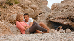 Young Couple is Resting in the Rocks near the Campfire Footage