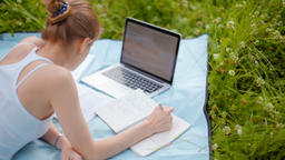 Nice Girl is Studying in Park with Laptop and Notebook in the Summer on Grass Footage