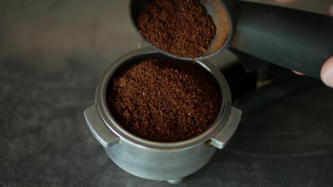 Grinded coffee in espresso handle - close-up Footage