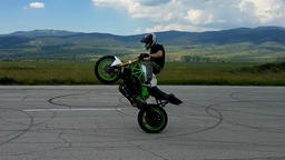 High end acrobatic biker in action training on an abandoned former air-strip Footage