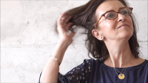 Middle aged woman fixing her hair in concrete background Footage