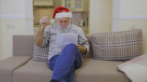 Senior man in Santa's hat reads family wish list on Christmas Footage