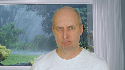 Face angry man looking in camera on background view from window on tropical rain GIF