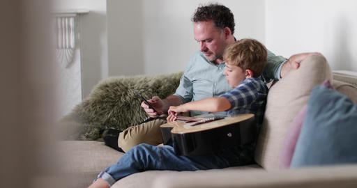 Father and Son watching a video tutorial on guitar playing Footage