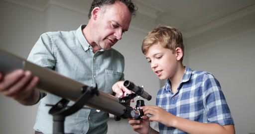 Father teaching Son how to use a telecsope Footage