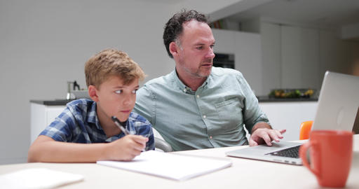 Father helping son with homework using a laptop Live Action