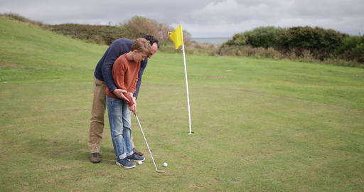 Father teaching son how to play golf Footage