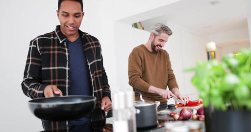 Adult male friends preparing a meal together Footage