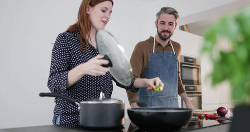 Couple tasting food whilst cooking Live Action