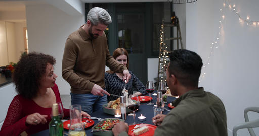Adult male serving Christmas meal to friends Footage