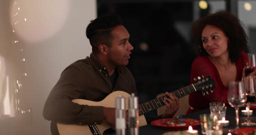 Man playing guitar at a dinner party Footage